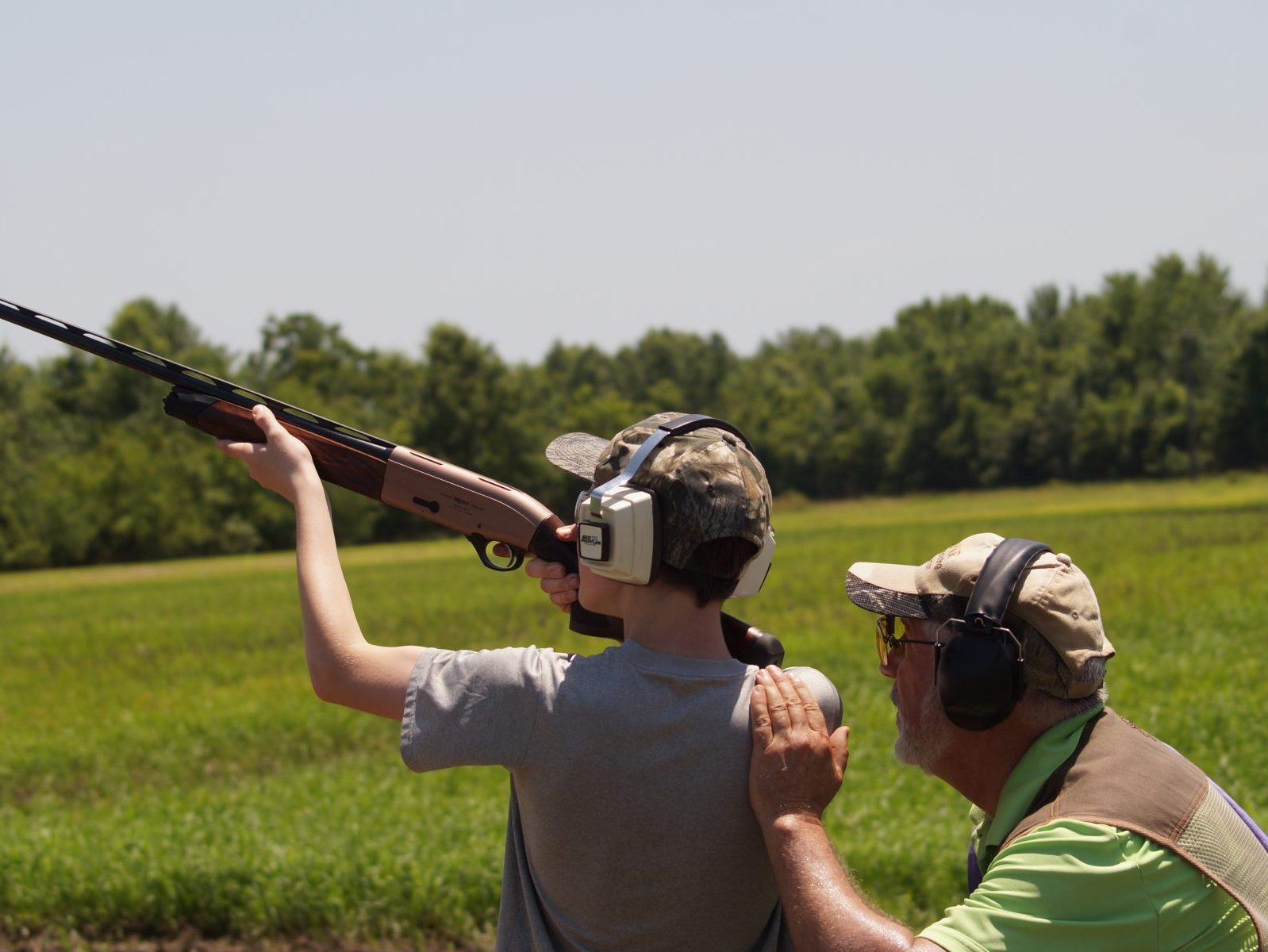 Young man learning to shoot from instructor at Gardner Camp